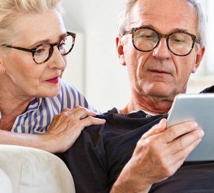 Due anziani seduti sul divano che utilizzano un tablet